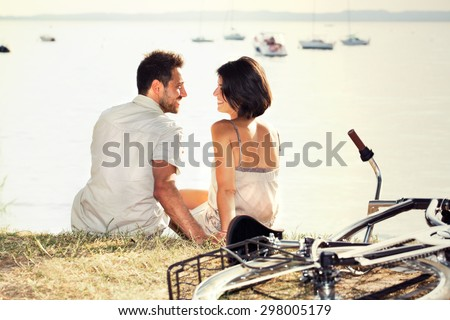 Couple with bicycle flirting in front of the lake