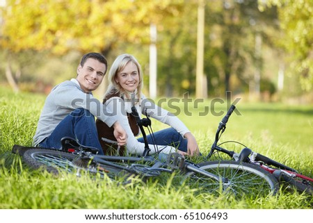 Couple with bicycles resting on the grass
