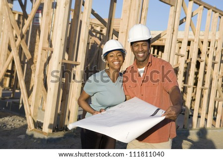 Couple with blueprint at construction site