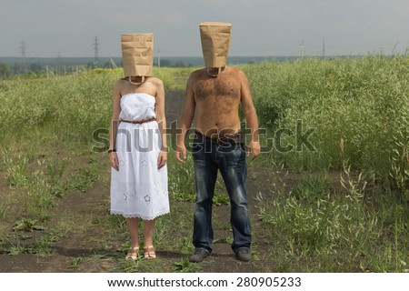 Couple with brown paper bags over their heads. Summer crazy concept.