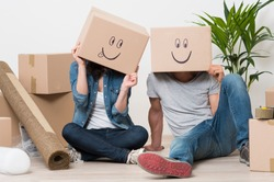 Couple With Cardboard Boxes On Their Heads With Smiley Face Sitting On Floor After The Moving House