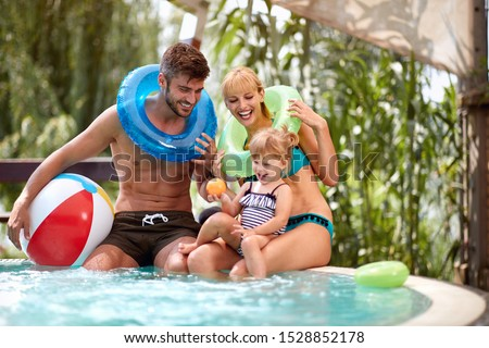 Couple with daughter enjoying on pool
