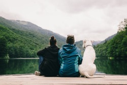 Couple with dog sitting on dock at the lake