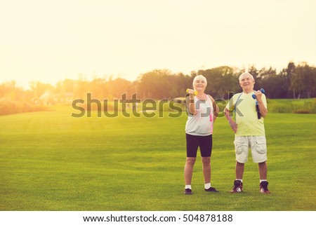 Couple with dumbbells smiling. Senior people standing outdoor. New training program for pensioners. Life and sports. #504878188