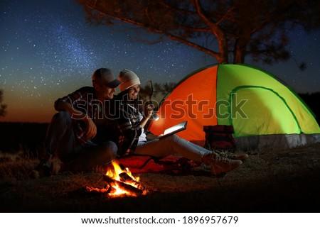 Couple with flashlight reading book near bonfire at night. Camping season Foto stock ©