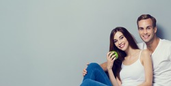 Couple with fruits, looking at camera with smile. Vegetarian, weight lossing, dieting, healthy food concept, on grey background, with copyspace for slogan or text.  Horizontal banner composition.
