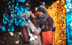 Couple with gift bag on Christmas lights background during walking in the city at evening