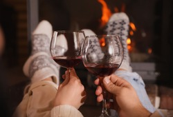 Couple with glasses of red wine near burning fireplace, closeup