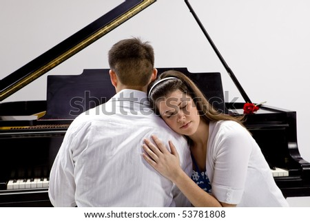 Couple with Grand piano 4 sitting at piano bench with red rose. - stock photo