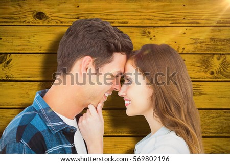 Couple with head against head and holding chin against green paint splashed surface #569802196