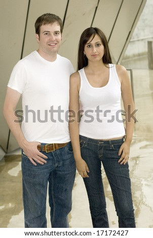 Couple with jeans and white tops posing outside