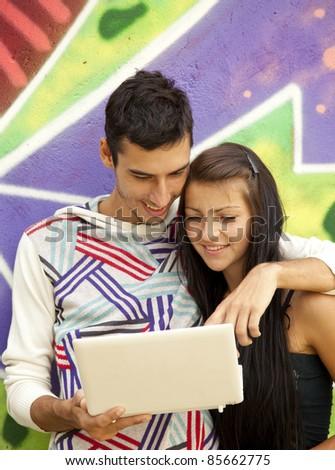 Couple with notebook near graffiti wall. Urban photo.