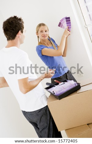 Couple with paint swatches in new home smiling - stock photo