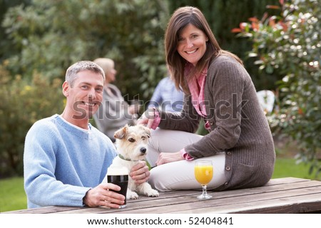 Couple With Pet Dog Outdoors Enjoying Drink In Pub Garden - stock photo