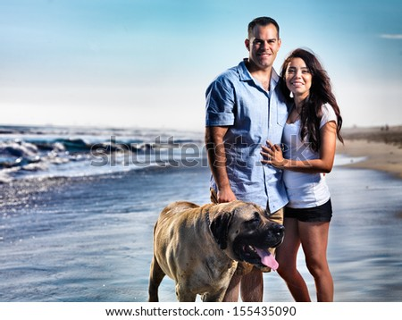 couple with pet dog posing on the beach.