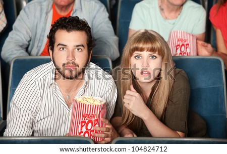 Couple with popcorn bag staring ahead in a theater - stock photo