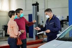 Couple with protective face masks giving car key to their auto repairman in a workshop.
