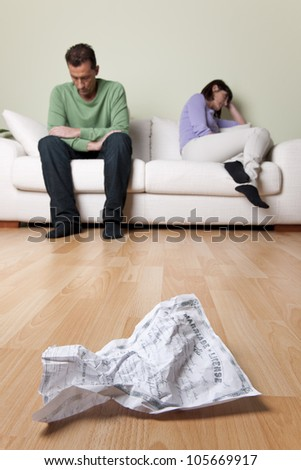 Couple with relationship problems, creased wedding certificate on foreground