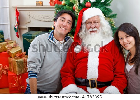 Couple with Santa smiling next to a Christmas tree
