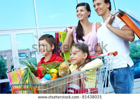 Couple with shopping bags pushing cart with two children - stock photo
