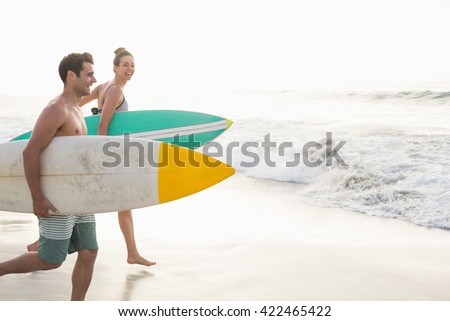 Couple with surfboard running on the beach on a sunny day