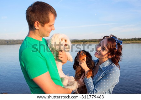 couple with their dogs on riverside, focus on girl\'s face