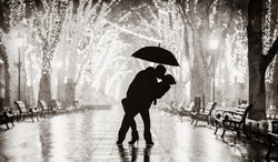 Couple with umbrella kissing at night alley. Image in back and white color style
