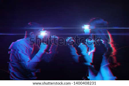 Couple with virtual reality headset are playing game and fighting. Image with glitch effect.