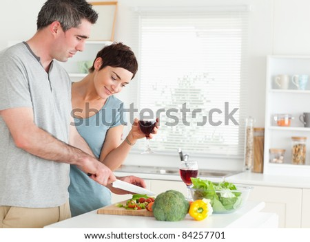 Couple with wine and vegetables in a kitchen - stock photo