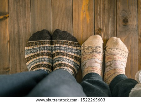 couple with woolen socks sitting on wooden floor, winter cosy scene #1522265603