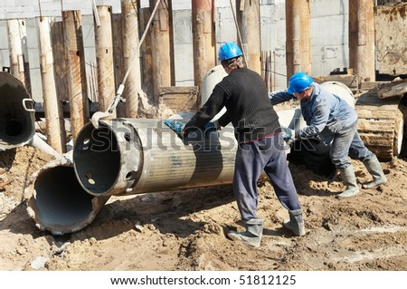 couple workers installing a tube metal form for piling with continuous concrete casting