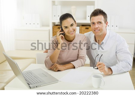 Couple working on laptop computer at home office, happy, smiling.