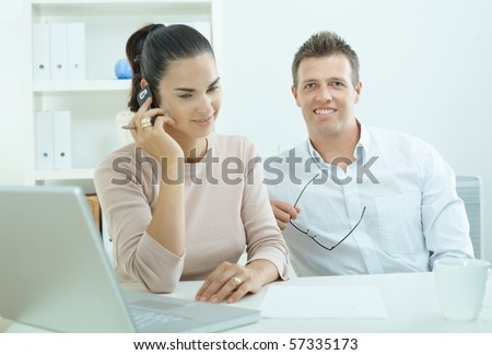 Couple working on laptop computer at home office, happy, smiling. Woman calling on mobile phone.