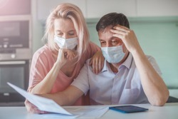 Couple worried about paperwork discuss unpaid bank debt calculate bills, shocked poor family looking at calculator counting loan payment upset about money problem during the pandemic coronavirus