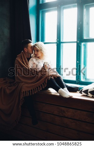 Couple wrapped in a woolen blanket, sitting and emracing next to blue colored window on windowsill. Pretty blonde woman holding a cup in her hands. Concept of love and relationship, family. #1048865825