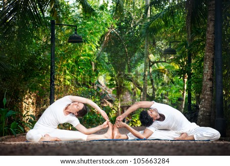 Couple Yoga of man and woman in white cloth doing parivrtta janu sirsasana Revolved Head to Knee pose in the garden