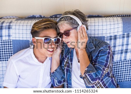 couple young and old grandmother and teenager nephew family time together listen music with earphones and enjoy the day. Happy family and generations different ages concept #1114265324