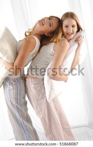 Couple young girl embracing pillow - stock photo