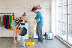 Couples doing chores. Young couple doing housework and chores the are enjoying doing chores together, mop and singing. Couple doing chores together, sweeping floor and smiling, and playing together.