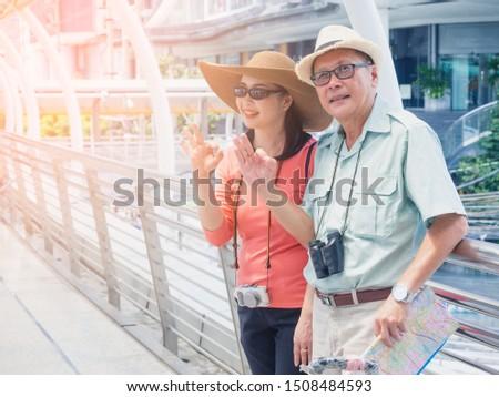 couples elderly travel in city,elder man and elder woman show sign ok