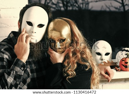 Couples in love. Woman and hipster in mask at window. Girl with long blond hair and man with beard hide face with masque. Decoration, amusement, disguise, pretense concept. Carnival, masquerade