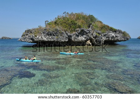 Couples kayaking by a beautiful island beach with pristine waters in the Hundred Islands, Philippines.