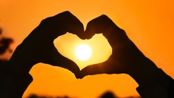 Couples Love hand heart in sunset background