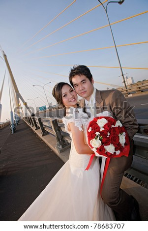 couples of happiness Bride and groom with beautiful rose bouquet on the road bridge