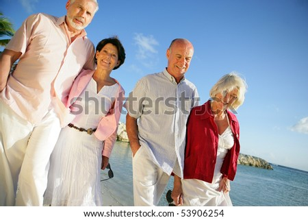 Couples of smiling seniors having a walk at the water's edge