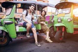 couples of young traveling people sitting on tuk tuk bangkok thailand