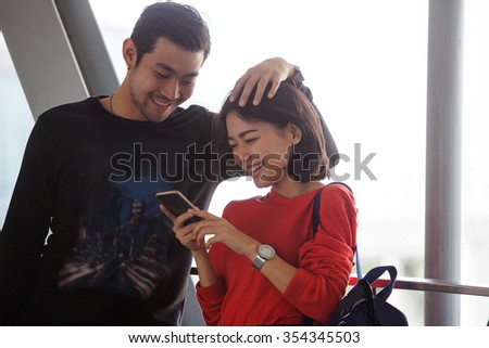 couples of younger asian man and woman relaxing with happy face reading text on smart phone use for people and modern lifestyle
