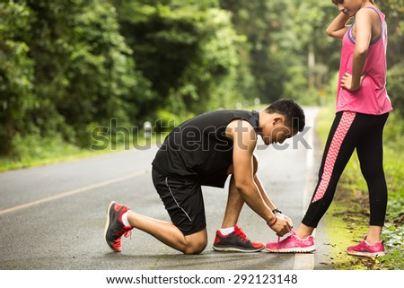 Couples runners Jogging Man tie his shoes to his girlfriend