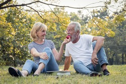 Couples senior give apples to each other together happily in the park. Concept of an elderly lover. Senior give apple to each other with smiling faces and happy.