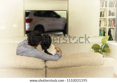 Couples sit on the sofa watching TV programs about cars and have a desire to use cars as transportation vehicles in the family.